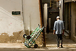 A man walks down a street near the Muscat Souq in Oman.