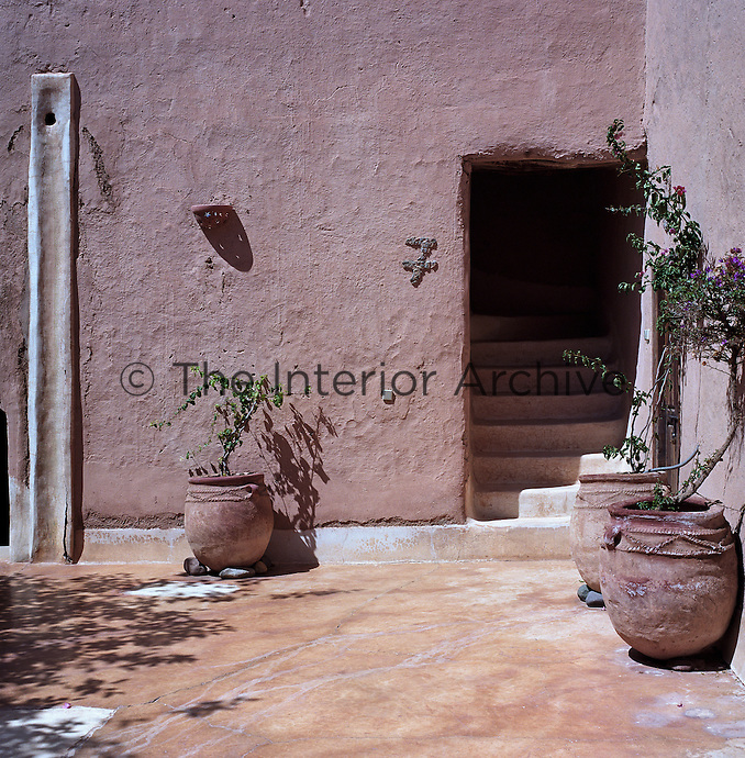 In a corner of a sun-filled courtyard bougainvillea grows from terracotta pots beside the entrance to suite 7