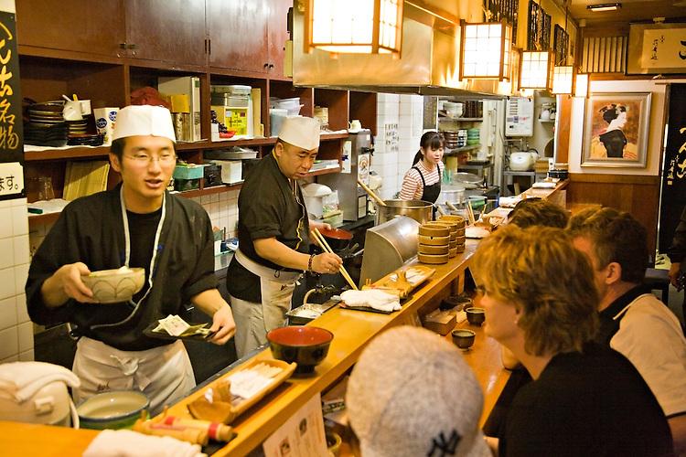Cooks serving food inside a Japanese restaurant in Kyoto Japan