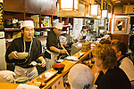 Cooks serving food inside a Japanese restaurant in Kyoto Japan