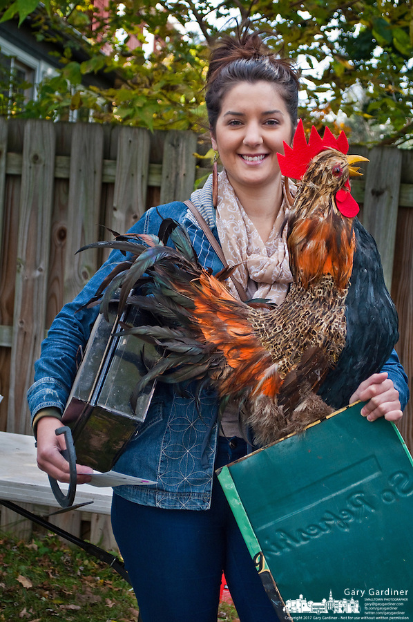 Jenna Growzinger holds a giant rooster and other items she bought at an estate auction...The contents of a home on East Broadway went before the auction block Saturday. ..Eager bargain hunters took their time looking over prospective purchases hoping others didn't know of its true value or weren't interested in their item of choice...Many boxed items were sold with the buyer only interested in one item in the box of interest. Many buyers bought large lots of glass and pottery for a single knickknack in the collection.