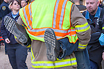 A firefighter carrying a patient to an ambulance.  shoes under arms