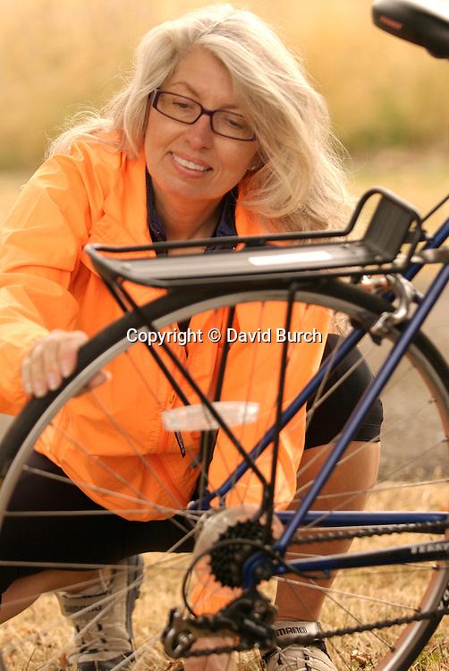 Mature woman looking at bicycle wheel, close-up