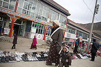 A tibetan woman of the Amdo region and her child walking along the street sellers in Xiahe.