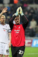 Pictured: Alan Tate of Swansea who substituted injured goalkeeper Dorus de Vries thanks his team's supporters after the final whistle. <br />