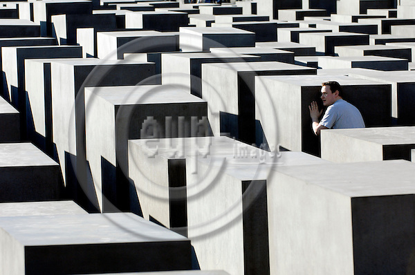 "BERLIN - GERMANY 12. 3. 2007 -- The Memorial to the Murdered Jews of Europe (German: Denkmal f?r die ermordeten Juden Europas), also known as the Holocaust Memorial (German: Holocaust-Mahnmal), is a memorial in Berlin to the Jewish victims of the Holocaust, designed by architect Peter Eisenman and engineers Buro Happold. It consists of a 19,000 square meter (4.7 acre) site covered with 2,711 concrete slabs or ""stelae"", arranged in a grid pattern on a sloping field. At the picture a boy stands between the pillars of the memorial -- PHOTO: GORM K. GAARE"
