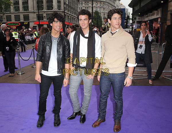 "JONAS BROTHERS - JOE JONAS, KEVIN JONAS & NICK JONAS .The UK Premiere of ""Jonas Brothers: The 3D Concert Experience"", Empire Leicester Square, London. .May 13th, 2009.full length black leather jacket scarf white top beige jumper brown tie jeans denim grey gray t-shirt waistcoat jeans denim.CAP/BEL.©Tom Belcher/Capital Pictures."