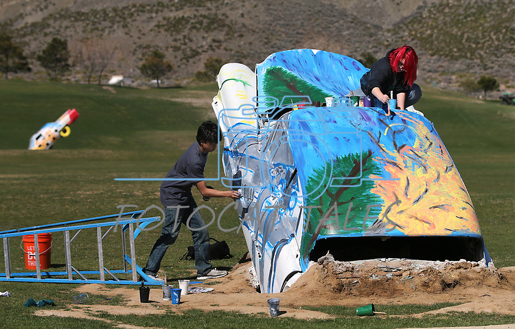 Doral Red Rock Academy students, Adela Del Rivero, and Denzel Barabaran, both 15, paint Cadillacs at the driving range at the Silver Oak Golf Course, in Carson City, Nev., on Sunday, April 8, 2018. The Las Vegas art students' work was a Carson City history theme. <br /> Photo by Cathleen Allison/Nevada Momentum
