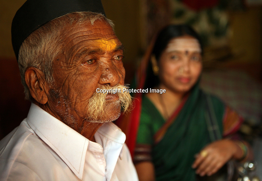 "Radhabai Madar Mudalagi (right) looks at her father who made the decision to dedicated her as a Devadasi at a very young age.  When asked how she feels about her parents' decision, she says ""they were poor and uneducated.  They didn't understand what they were doing"".  Now in her early forties, she lives in the small village of Yellamanawadi and uses the Devadasi musical tradition called ""Chowdike Pada"" to educate her audiences about social issues, particularly, the Devadasi system. Accompanied by her husband, Mrutunjaya Mudalagi who plays an instrument called the shruti that resembles a guitar, Radhabai was even recorded for a television program which was broadcasted to small villages all over Karnataka and other states as part of a social education program.  Because of her activism coupled with the fact that she defied the Devadasi system and married a man, she has been rejected by her community.."
