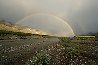 A double rainbow forms on a summer evening over the Hulahula River at Grasser's Strip in Alaska's Arctic National Wildlife Refuge, where campers have tipped their rafts on edge to act as wind blocks.