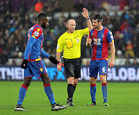 Scott Dann of Crystal Palace (R) protests to match referee Mike Dean (C) for awarding a foul to Swansea during the Barclays Premier League match between Swansea City and Crystal Palace at the Liberty Stadium, Swansea on February 06 2016