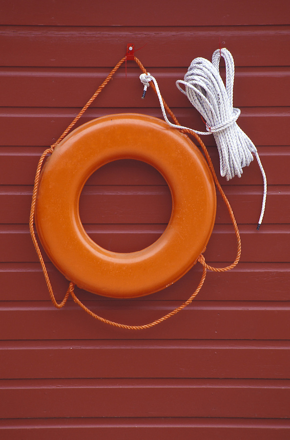 Life ring hanging on red wall