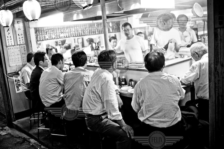 """Salarymen flock to a late night food stand in Tokyo. """"My husband always worked late and rarely ate dinner with family. He was absent from family life. We lived like a single-mother household"""" says Kinmi Ohashi, 60, whose husband, Hitoshi committed suicide."""