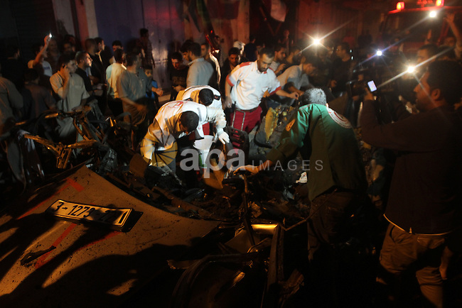 Palestinian rescuers check a car hit by an Israeli air strike in Gaza City on July 09, 2014. A Palestinian working for a local news agency in the Gaza Strip was killed on Wednesday night by an Israeli strike on a car full of journalists, according to multiple reports from the war-torn region. Photo by Yasser Qudih