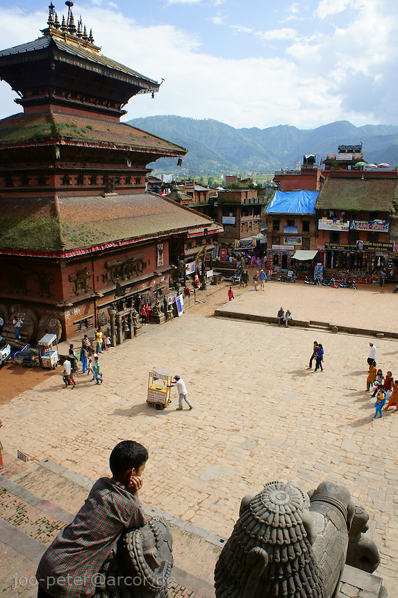 Taumadhi Tol Square in Bhaktapur,Nepal, looking at Bhairavnath  temple with typical pagode-style architecture, shot on the stairs of Nyataponla temple with view on stone sculpture and boy, in the background and  typical landscape with mountains surrounding Kathmandu valley.