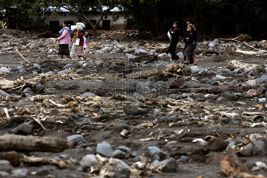 A family walks over an area that mudslides destroyed earlier in the month when Hurricane Stan spawned torrential rains over parts of Central America. Hundreds of people and houses were buried in the mudslide that caught the area of Lake Atitl&aacute;n by surprise in the early morning hours.<br />