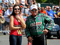 Aug. 2, 2014; Kent, WA, USA; NHRA funny car driver John Force (right) with wife Laurie Force during qualifying for the Northwest Nationals at Pacific Raceways. Mandatory Credit: Mark J. Rebilas-USA TODAY Sports