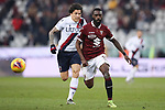 Nicolas Nkoulou of Torino FC races after the ball with Federico Santander of Bologna in pursuit during the Serie A match at Stadio Grande Torino, Turin. Picture date: 12th January 2020. Picture credit should read: Jonathan Moscrop/Sportimage