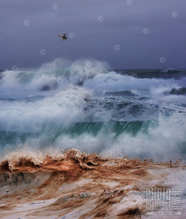 A Honolulu Fire Department helicopter hovers over the Banzai Pipeline off of Ehukai Beach Park on the North Shore of O'ahu.
