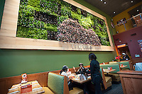 "The grand opening of the new Applebee's casual dining restaurant in the East River Plaza shopping center in New York is seen on Monday, December 10, 2012. The new restaurant, which is applying for LEED Gold certification, uses rainwater collected from the roof, waterless urinals and contains a ""Living Wall"" of plants to help purify the air among other eco-friendly features. (© Richard B. Levine)"