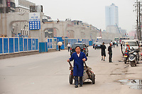 Daytime landscape view of a man pulling a hand cart near the Wuhan Metro Line Number Three construction site on Fa Zhan Da Dao near the Hankou Railway Station in Hànkǒu in the Jiānghàn Qū in Hubei Province.  © LAN