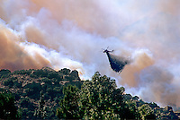 870000360 a los angeles county fire fighting helicopter performs an aerial retardant drop on a burning hillside in the path of the topanga fire in the hills above the san fernando valley in southern california