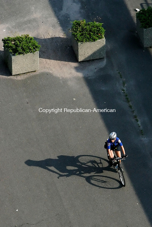 WATERBURY, CT, 07 July 2006- 070706BZ01- A Waterbury Police officer on bicycle patrol rides through the parking area of the train station on Meadow Street Friday afternoon.<br /> Jamison C. Bazinet Republican-American
