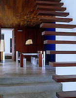 The iroko wood steps leading up from the dining area give a sense of layering to the building