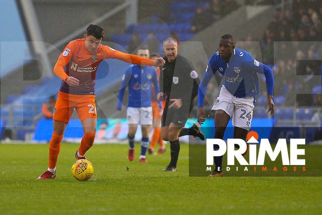 Northampton Town's Regan Poole (L) has a shot at goal despite the attentions of Oldham Athletic's Ousmane Fane (R) during the Sky Bet League 1 match between Oldham Athletic and Northampton Town at Boundary Park, Oldham, England on 9 December 2017. Photo by Juel Miah / PRiME Media Images.
