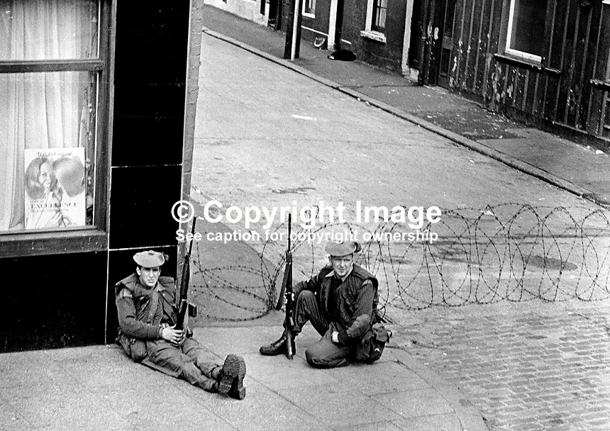 Two soldiers on a street corner monitor the Lower Falls Road Curfew. 197007030251h...The British Army imposed during July 3 & 4, 1970, a 34 hour curfew (except for a two hour break to allow shopping) in approximately 50 streets in the Lower Falls district of Belfast, N Ireland, UK. A military helicopter hovered overhead warning people they would be arrested if they remained on the streets. An army search during the curfew uncovered 100 firearms, 100 home-made bombs, 250 lbs of explosives, 21000 rounds of ammunition and 8 two-way radios. This curfew is often seen as a turning point in souring relations between the Roman Catholic working class and the British Army. The army was no longer seen as the protector of the Catholic community...Copyright Image from Victor Patterson, 54 Dorchester Park, Belfast, UK, BT9 6RJ..Tel: +44 28 9066 1296.Mob: +44 7802 353836.Voicemail +44 20 8816 7153.Skype: victorpattersonbelfast.Email: victorpatterson@mac.com.Email: victorpatterson@ireland.com (back-up)..IMPORTANT: If you wish to use this image or any other of my images please go to www.victorpatterson.com and click on the Terms & Conditions. Then contact me by email or phone with the reference number(s) of the image(s) concerned.
