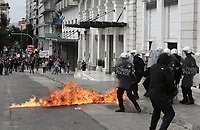 Pictured: Riot police officers try to put out a fire from a petrol bomb Wednesday 17 May 2017<br /> Re: Clashes between anti fourth memorandum protesters and riot police during 24 hour strike in Athens, Greece