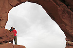Couple standing at North Window Arch in Arches National Park, Moab, Utah, USA. .  John offers private photo tours in Arches National Park and throughout Utah and Colorado. Year-round.