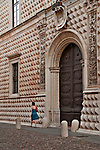 A woman passes by the main entrance of the Palazzo dei Diamanti, originally a residential home of the Este family (built between 1493 and 1503) and acquired by the city in 1832, the palace is now the National Gallery of Art and Civic University