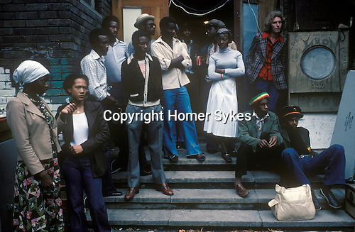 Black community Notting Hill west London 1970s England UK.  Local people standing outside sort of community building that was being used for the Carnival. The sound system was being run from within the building. The people look the way they do - apprehensive, concerned - because some trouble was just starting up and groups of youths were starting to run through the crowds of revelers.