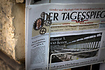 An edition of local newspaper Der Tagesspiegel in a newsagent shop outside the disused Tempelhof airport in Berlin, Germany. The historic airfield was constructed in 1923, used by the Nazis for rallies and became the site of the American airlift during the blockade of West Berlin  by the USSR. In October 2015, giant hangars were converted into temporary accommodation space for hundreds of refugees arriving in Berlin.