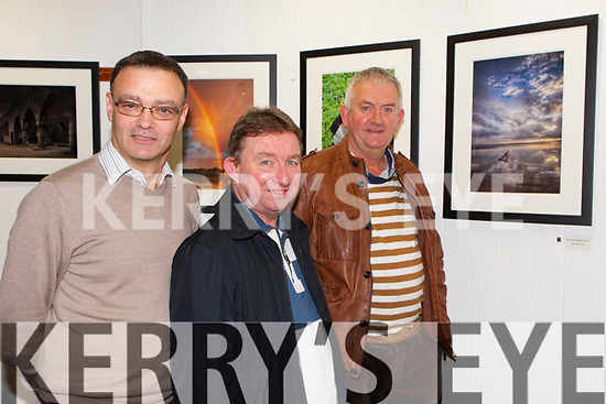 Seamus Long, Teddy Sugrue and John Keane looking at the launch of their Photo exhibition in Killarney Library on Thursday evening
