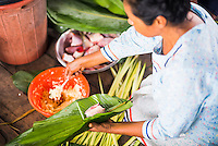 Woman preparing traditional dish of fish wrapped in banana leaves, Amazon Rainforest, Coca, Ecuador, South America
