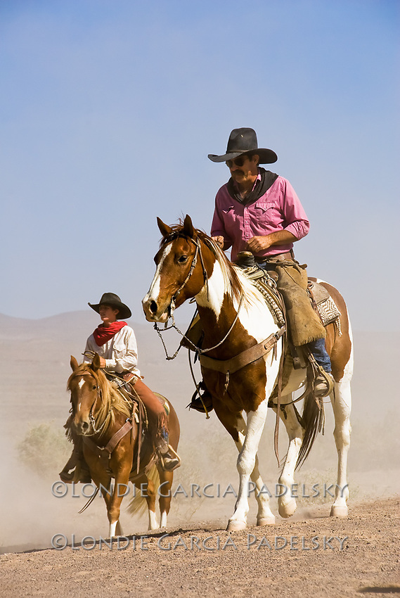 Two cowboys riding horses at a cattle drive in the Owens Valley, California