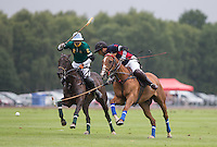 Marcos Di Paola (King Power) hits the ball past Juan Gris Zaveleta (Salkeld) during the Cartier Queens Cup Final match between King Power Foxes and Dubai Polo Team at the Guards Polo Club, Smith's Lawn, Windsor, England on 14 June 2015. Photo by Andy Rowland.