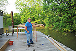 "8/11/11} Vicksburg} -- Vicksburg, MS, U.S.A. -- Mark Bridges,56, thrift store owner,looks out at what used to be his front yard now covered oin over 15 ft of water from the Mississippi river flooding. and his dog ""baby girl"" and his girlfriend of 12 years Patricia Clark, a homeDepot garden employee, cruise down Chicksaw Rd in a bass boat in North Kings Community in Vicksburg Mississippi Wed. May 5th 2011. This is the firs time for Patricia to try and remove things from her trailer, that is built on 9ft stilts  AND THE WATER IS CURRENTLY AT 15 ft. and rising and is less than 12 inches from being flooded. Mark and Patricia have lived their all their lives and will return when the Mississippi River recedes,. ark has been helping his neighbors get their belongings to safety. Vicksburg a riverfront town steeped in war and sacrifice, gets set to battle an age-old companion: the Mississippi River. The city that fell to Ulysses S. Grant and the Union Army after a painful siege in 1863 is marshalling a modern flood-control arsenal to keep the swollen Mississippi from overwhelming its defenses. PHOTO©SUZIALTMAN.COM.Photo by Suzi Altman, Freelance."