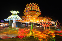 AUGUSTA, NJ - AUGUST 13: Colorfully illuminated rides, including the Sizzler in the foreground, spin against the night sky during the New Jersey State Fair on August 13, 2010 at the Sussex County Fairgrounds, Augusta, New Jersey