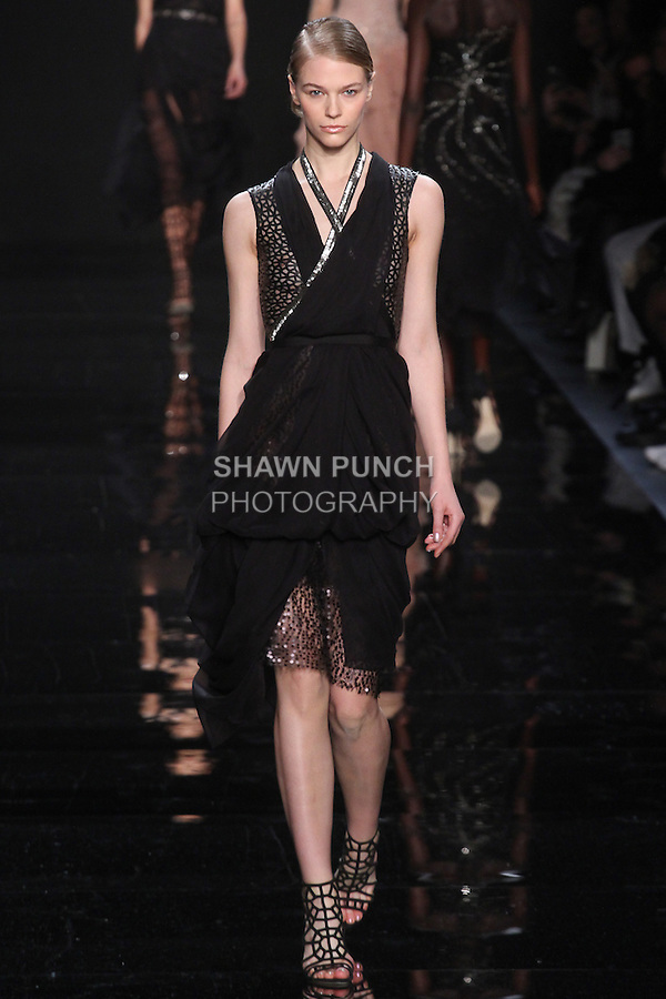 """Model walks runway in a black laser cut leather dress with draped silk chiffon skirt and embroidered detail from the Reem Acra Fall 2016 """"The Secret World of The Femme Fatale"""" collection, at NYFW: The Shows Fall 2016, during New York Fashion Week Fall 2016."""