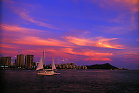 A beautiful sunset with Waikiki beach and Diamond head with with sail-like cloud formations and sailboat