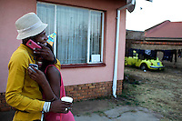 SOWETO, SOUTH AFRICA: A couple shares a friendly moment during a birthday party in a house in Kliptown section of Soweto, South Africa. Soweto is South Africa's largest township and it was founded about one hundred years to make housing available for black people south west of downtown Johannesburg. The estimated population is between 2-3 million. Many key events during the Apartheid struggle unfolded here, and the most known is the student uprisings in June 1976, where thousands of students took to the streets to protest after being forced to study the Afrikaans language at school. Soweto today is a mix of old housing and newly constructed townhouses. A new hungry black middle-class is growing steadily. Many residents work in Johannesburg, but the last years many shopping malls have been built, and people are starting to spend their money in Soweto.  (Photo by Per-Anders Pettersson)