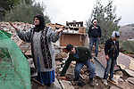 Palestinians search through the debris of a shed destroyed by Israeli soldiers with bulldozer near the Jewish settlement of Gharsina close to the West Bank town of Hebron 31 December 2009. According to witnesses, the structure was demolished due to a lack of permits.Photo by Najeh Hashlamoun