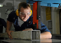071101-N-7981E-023 Pacific Ocean (November 1, 2007)- Aviation Structural Mechanic 3rd Class Christopher Hoard uses a band saw to cut apart a damaged tow bar tongue in the Aviation Intermediate Maintenance Department (AIMD) Sheet Metal Shop aboard Nimitz-class aircraft carrier USS Abraham Lincoln (CVN 72). Lincoln and embarked Carrier Air Wing (CVW) 2 are underway off the coast of Southern California participating in Composite Training Unit Exercise (COMPTUEX), an exercise designed to enhance the interoperability between Lincoln and its strike group. U.S. Navy photo by Mass Communication Specialist 3rd Class James R. Evans (RELEASED)