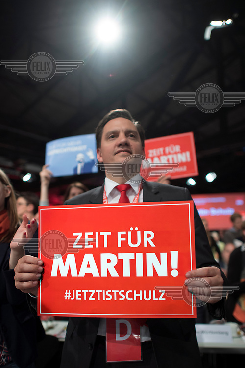 An SPD member holds a sign supporting the party leader, Martin Schulz, during his speech during the party conference. Schulz is the SPD's candidate for chancellor in the 2017 federal election.