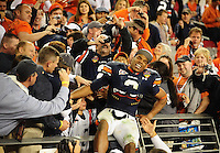 Jan 10, 2011; Glendale, AZ, USA; Auburn Tigers quarterback (2) Cameron Newton grimaces in pain after going into the grandstands to hug his father Cecil Newton (not pictured) following the victory over the Oregon Ducks in the 2011 BCS National Championship game at University of Phoenix Stadium.  Mandatory Credit: Mark J. Rebilas-