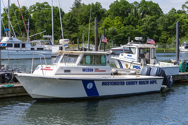 A boat used by the Westchester County Health Department for code enforcement docked in the West Basin of Mamaroneck Harbor in Harbor Island Park, located in Mamaroneck, New York.
