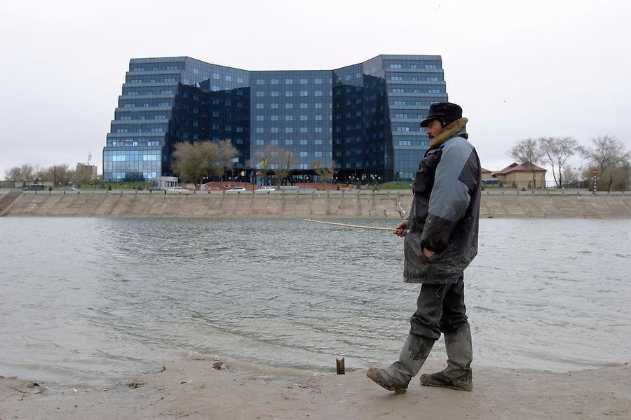 Atyrau, Kazakhstan, 14/11/2003..Unemployed men engage in subsistance fishing with the new River Palace 5 star hotel amd office complex occupied by foreign oil companies behind.